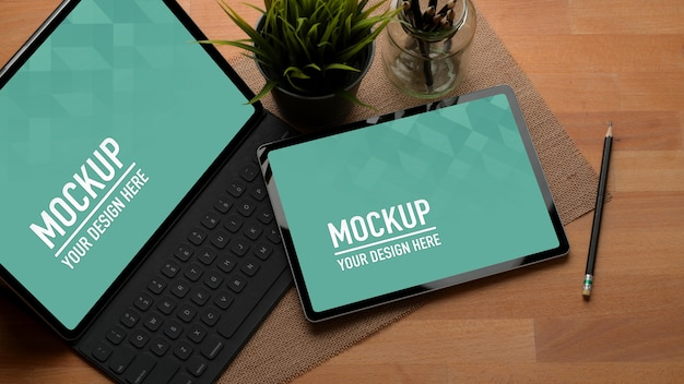 Ritagliata colpo di tavolo da lavoro con due mock up tavolette digitali e matite nella stanza dell'home office