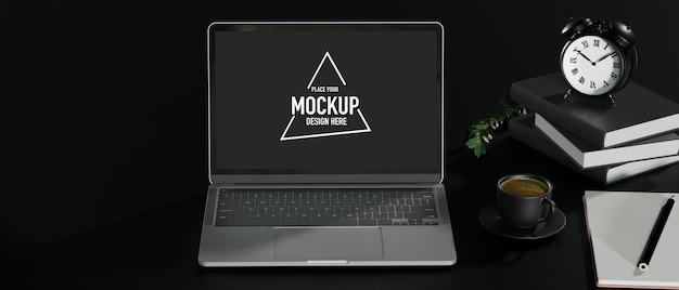 Spazio di lavoro in ufficio scuro con mockup di laptop aperto e accessori su sfondo nero da tavolo