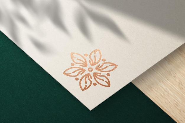 Mockup logo impresso su carta color crema con effetto lamina di bronzo premium psd