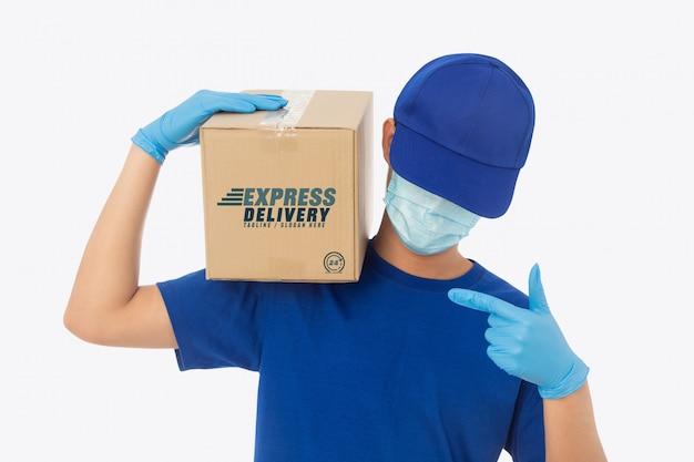 Mano del fattorino in guanti medici e maschera d'uso che tiene il modello della scatola di cartone