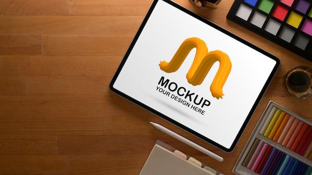 Area di lavoro di design con tablet mockup e strumenti di pittura