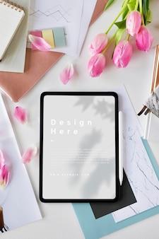 Modello di tablet digitale su un tavolo con fiori