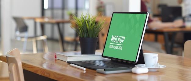 Mockup di tavoletta digitale con accessori sulla tavola di legno