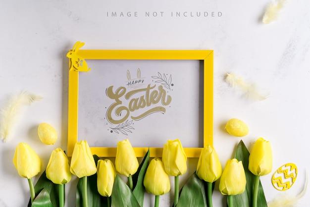 Uova di pasqua con tulipani e mockup di cornice per foto gialla