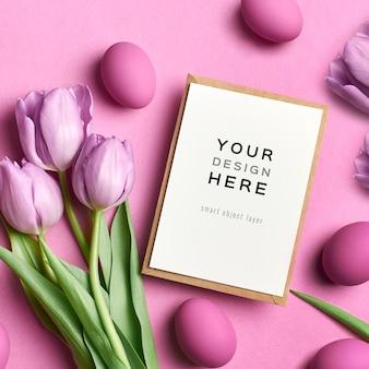 Mockup di cartolina d'auguri di festa di pasqua con uova colorate e tulipani sul rosa