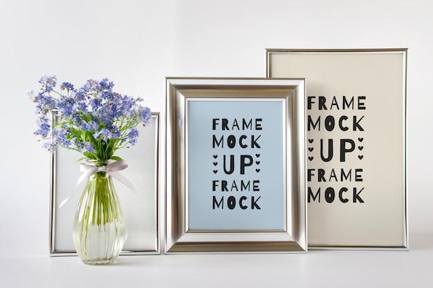 Modello di mockup psd modificabile con composizione di tre cornici d'argento e fiori blu