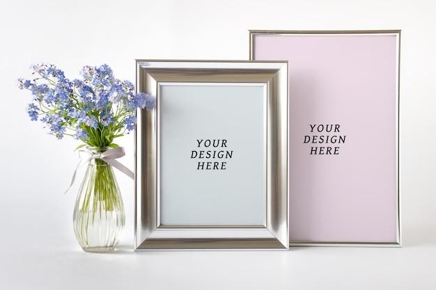 Modello di mockup psd modificabile con due cornici vuote d'argento e fiori selvatici blu in un vaso di vetro.