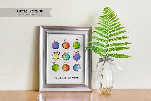 Mockup psd modificabile con cornice d'argento a5 vuota con bordo largo e foglia di felce in vaso di vetro
