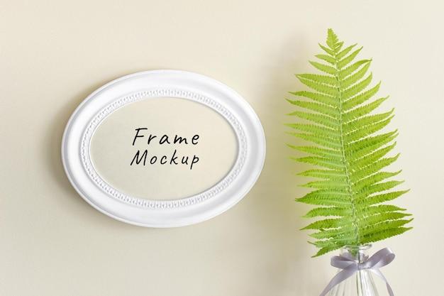 Mockup psd modificabile con cornice orizzontale ovale rotonda e foglia di felce selvatica della foresta in vaso di vetro