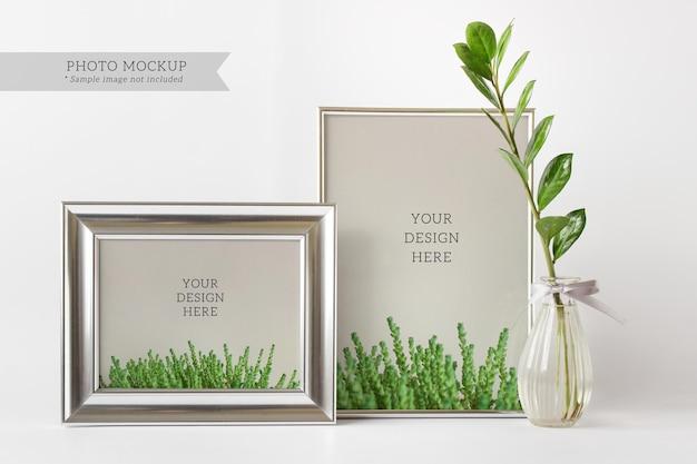 Mockup psd modificabile con due cornici d'argento vaso di vetro con ramo di pianta zamioculcas