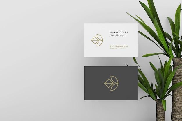 Elegante modello di biglietto da visita scuro e bianco con piante come sfondo