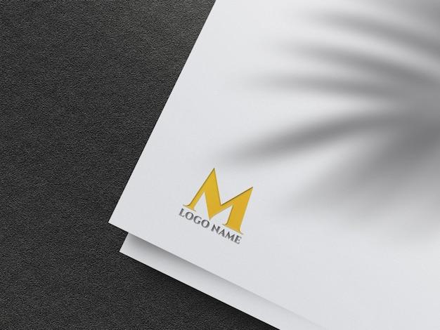 Mockup logo dorato in rilievo su carta bianca