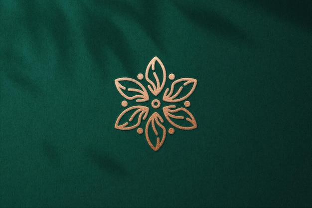Mockup logo in rilievo con lamina di bronzo su carta verde premium psd