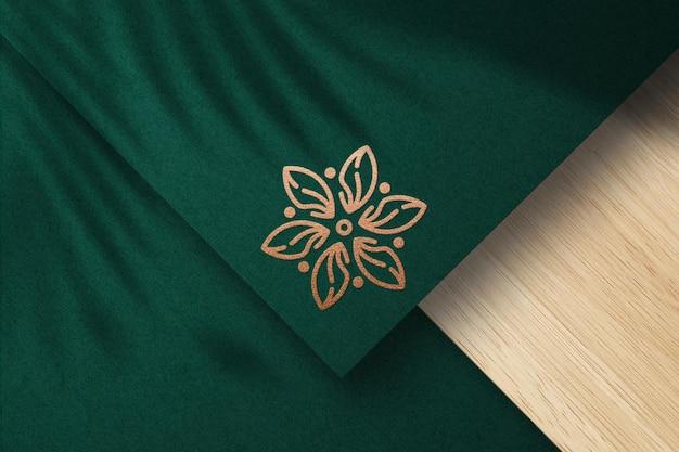Mockup logo in rilievo con lamina di bronzo su carta verde