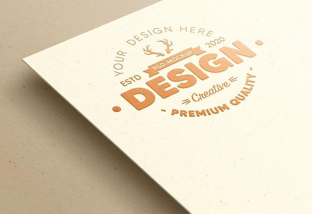 Logo mockup in rilievo su carta bianca con lamina di bronzo