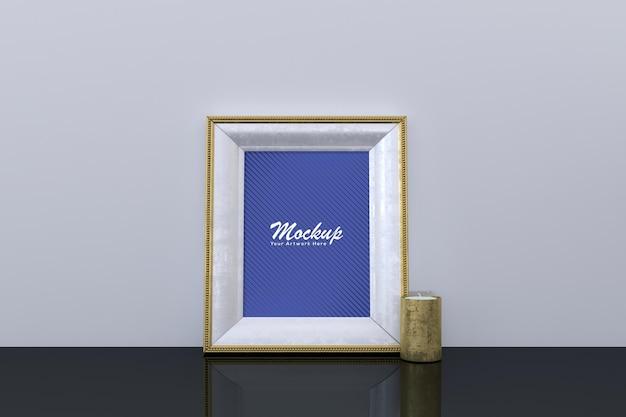 Mockup di cornice per foto dorata vuota con candela sul pavimento scuro