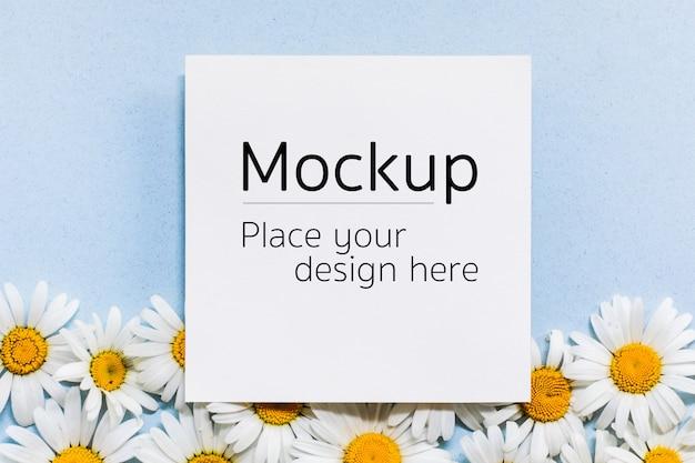 Mockup di carta nota vuota con fiori di camomilla