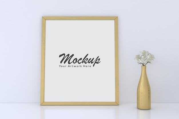 Mockup di cornice per foto vuota con vaso d'oro