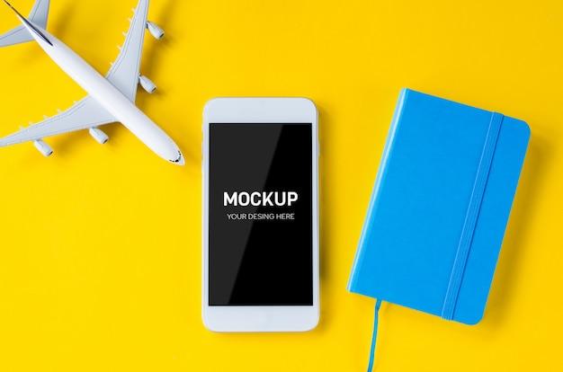 Smartphone a schermo vuoto, aeroplano decorativo e taccuino, modello per la presentazione di app.