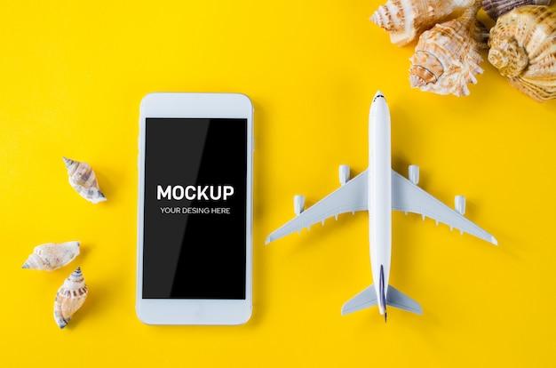Smartphone a schermo vuoto, aeroplano decorativo e conchiglie, modello per la presentazione di app.