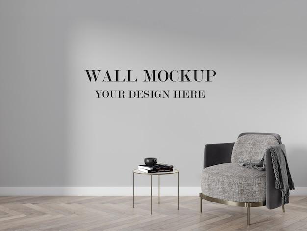 Mockup di muro vuoto dietro la moderna poltrona grigia