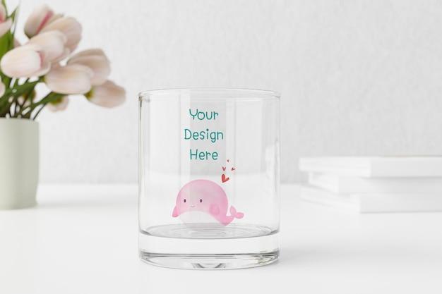 Mockup di bicchiere d'acqua vuoto sul tavolo con i tulipani