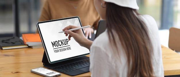 Studentessa universitaria facendo assegnazione con tablet e smartphone mockup