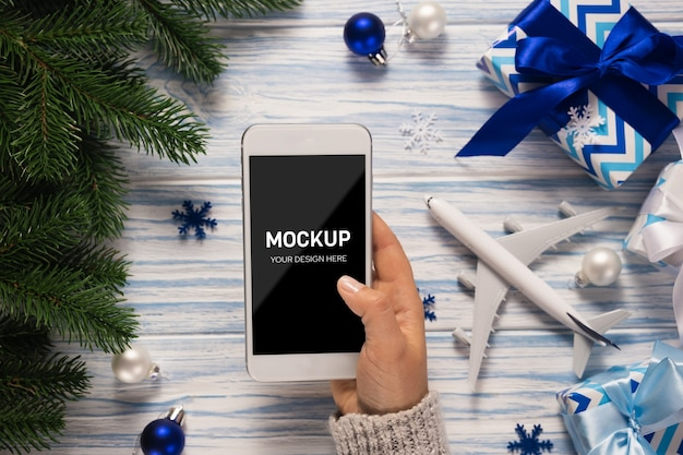 Mano femminile che tiene uno smartphone tra decorazioni natalizie e modello di aereo