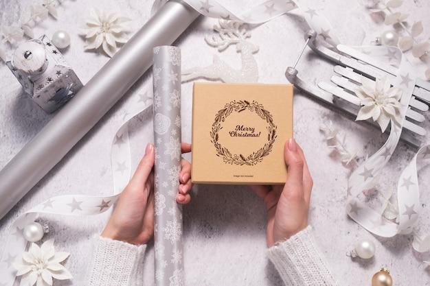 Le mani femminili tengono una confezione regalo per l'imballaggio in argento e bianco per natale. modello