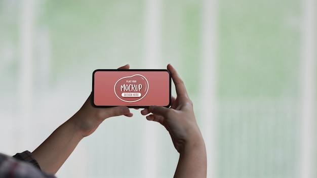 Mani femminili che tengono mock up schermo smartphone orizzontale