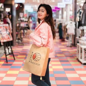 Donna che cammina nel centro commerciale con la borsa della spesa