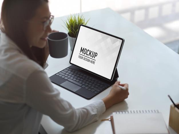 Donna che lavora con il mockup di tavoletta digitale