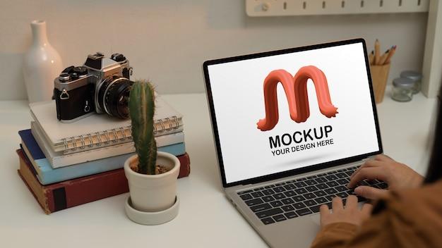Donna che lavora con il computer portatile mockup sulla scrivania dell'ufficio domestico