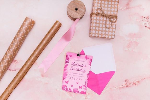 Disposizione piatta del mock-up regalo di compleanno con carta e busta