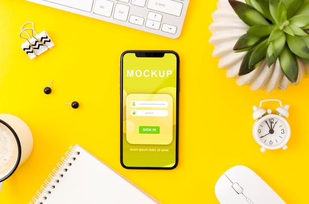 Mock-up di telefono piatto laici sulla scrivania con pianta