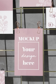 Cartoline floreali appese su una griglia metallica con clip rosa