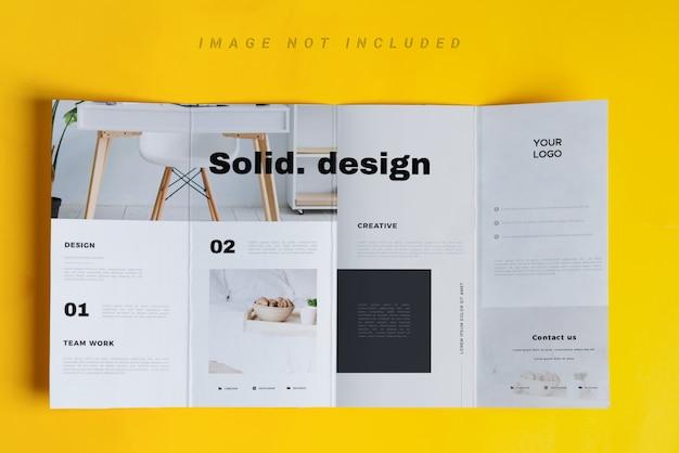 Modello di brochure a quattro volte sul tavolo giallo