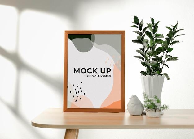 Mockup di arte della parete con cornice in soggiorno e piante in vaso con ombra della finestra sul muro bianco.