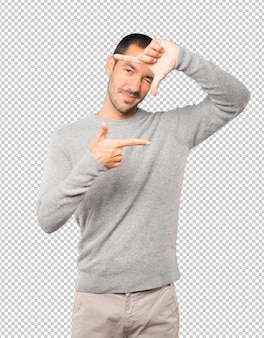 Amichevole giovane che fa un gesto di scattare una foto con le mani