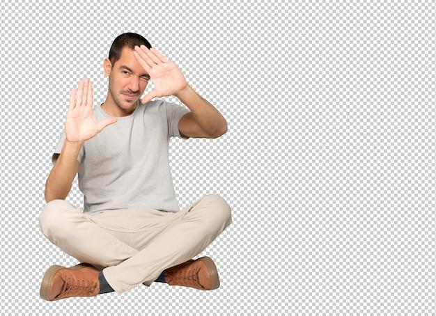 Gentile giovane uomo che fa un gesto di scattare una foto con le mani