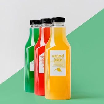Vista frontale dell'assortimento di bottiglie di succo trasparenti con tappi