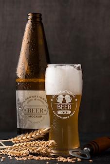 Vista frontale del bicchiere di birra e bottiglia con orzo