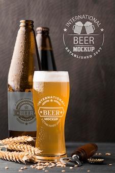 Vista frontale del bicchiere di birra e bottiglie con orzo