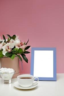 Modello in bianco di vista frontale del telaio della foto sulla tavola rosa. fiori di orchidea, tazza di tè e dolci.