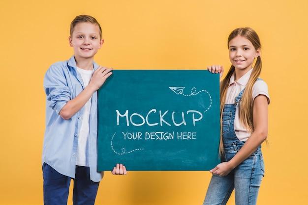 Bambini felici di vista frontale che tengono segno di mock-up