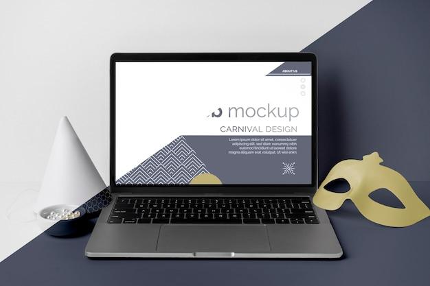 Vista frontale del mock-up di carnevale minimalista con maschera, laptop e cono