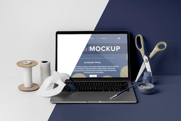 Vista frontale del mock-up di carnevale minimalista con forbici e laptop