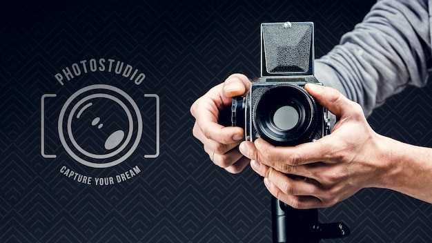 Vista frontale del fotografo che regola macchina fotografica