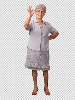 Donna senior dell'ente completo allegra e sicura facendo gesto giusto, eccitato e urlando