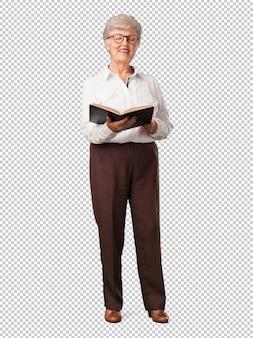 Full body senior woman concentrato e sorridente, con in mano un libro di testo, studiando per superare un esame o leggere un libro interessante